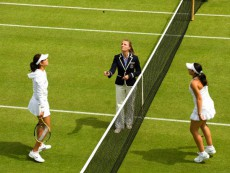 The umpire tosses the coin before the start of the Julia Goerges v Marion Bartoli match on Court 18 at the Wimbledon Tennis Championships 2010.
