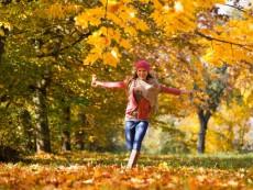 Austria, Teenage girl running on autumn leaf