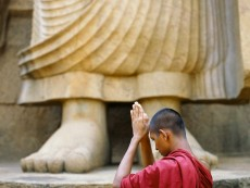 Buddhist monk praying next to Aukana Buddha