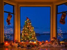 Christmas Tree with lights, decorations, and gifts in a window at dusk, The Artists Point, Hyde Creek, Port McNeill, Northern Vancouver Island, Vancouver Island, British Columbia, Canada.