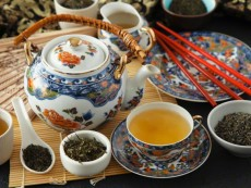 A still life featuring green tea (teapot, cups, tea leaves)