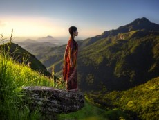 Girl wearing sari at the edge of a rock enjoying the view of a landscape in Ella, Sri Lanka