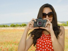 Young woman with camera in poppy field