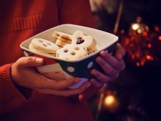 Girl holding bowl with Christmas cookies