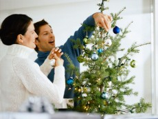 Couple decorating Christmas tree with ornaments